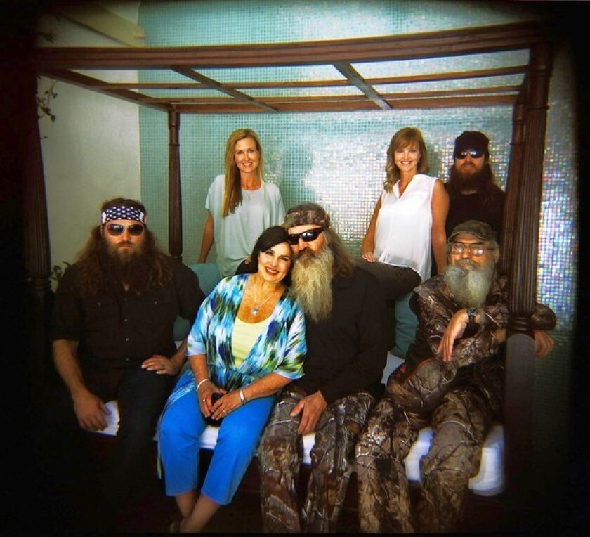 """""""Duck Dynasty"""" on A&E features Willie, left, his wife, Korie, matriarch Kay and her husband, Phil, Missy and her husband, Jase (background) and Si."""