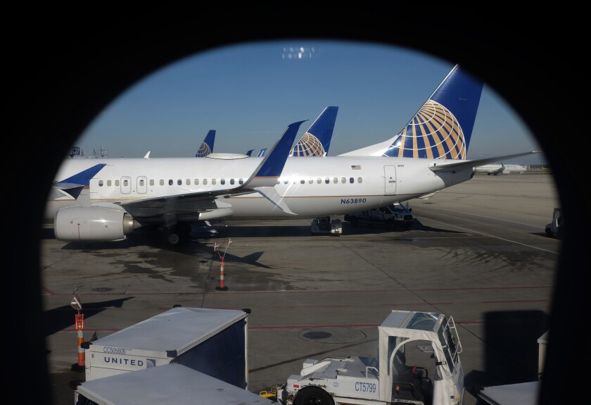 In this Nov. 22, 2017, photo taken through an aircraft passenger window, United Airlines planes are parked at a terminal at O'Hare International Airport in Chicago.