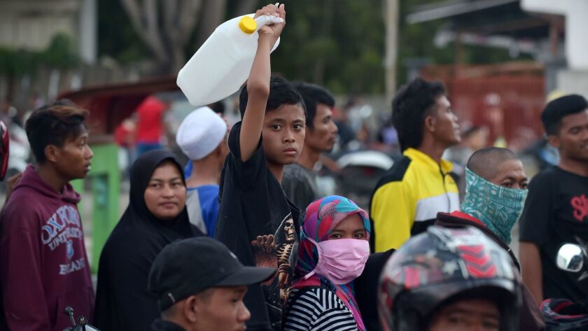 People queue for gasoline in Palu, Indonesia's Central Sulawesi on Monday.