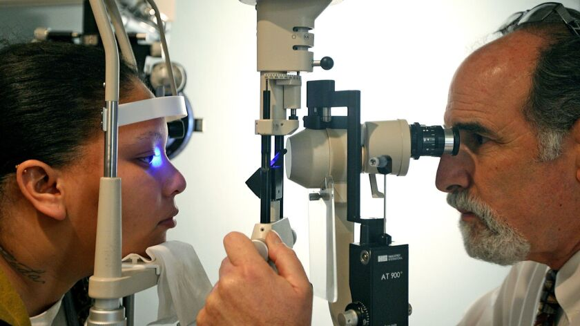 optometrist uses technology to exam a low vision patient
