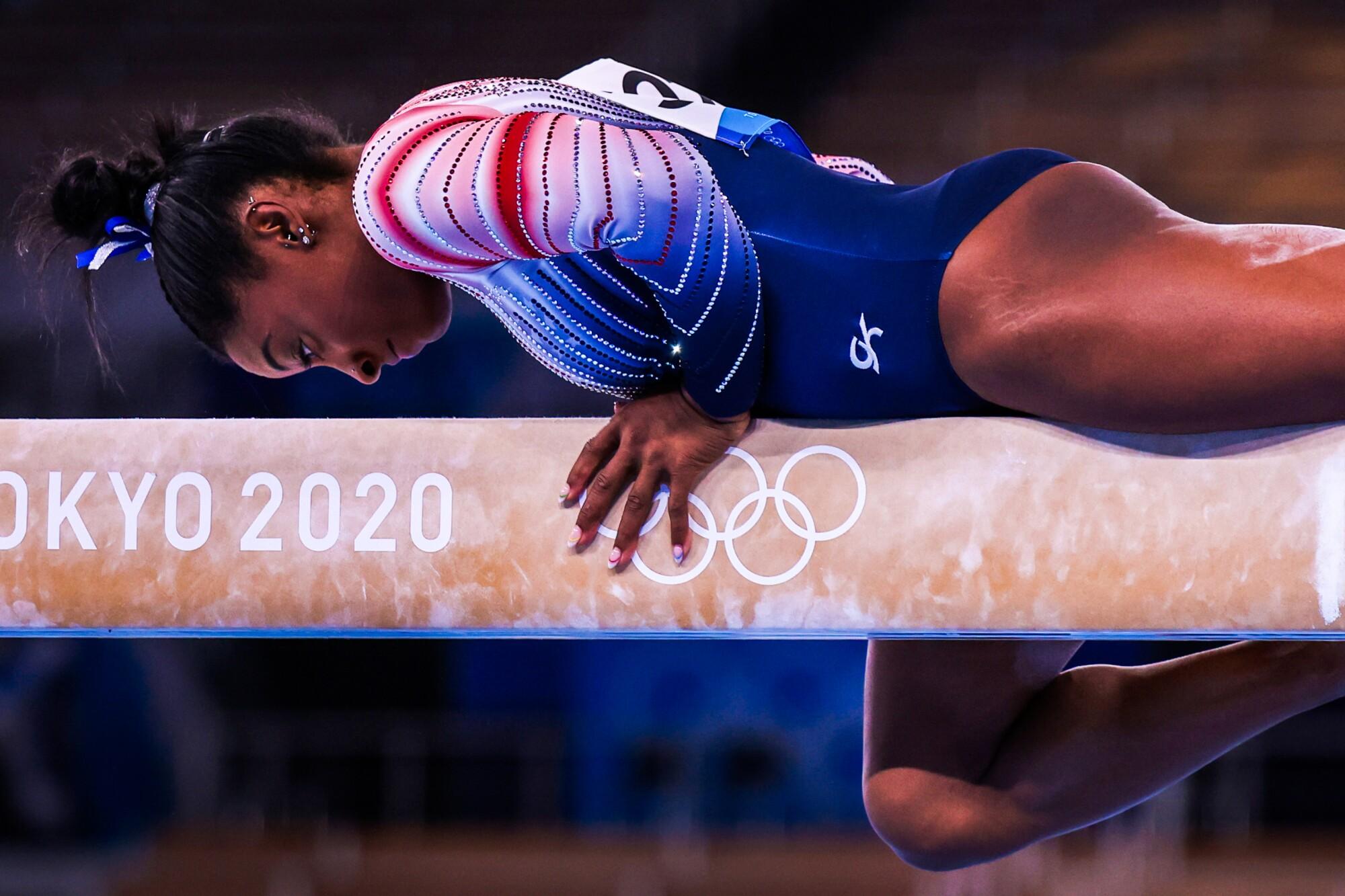 Simon Biles lies on the balance beam during her routine.