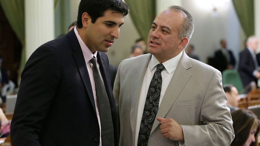 Former Assemblyman Raul Bocanegra (D-Pacoima), right, discusses a bill with Assemblyman Matt Dababneh (D-Woodland Hills) at the Capitol in Sacramento in 2014. Both men have decided to resign while facing allegations of sexual harassment.