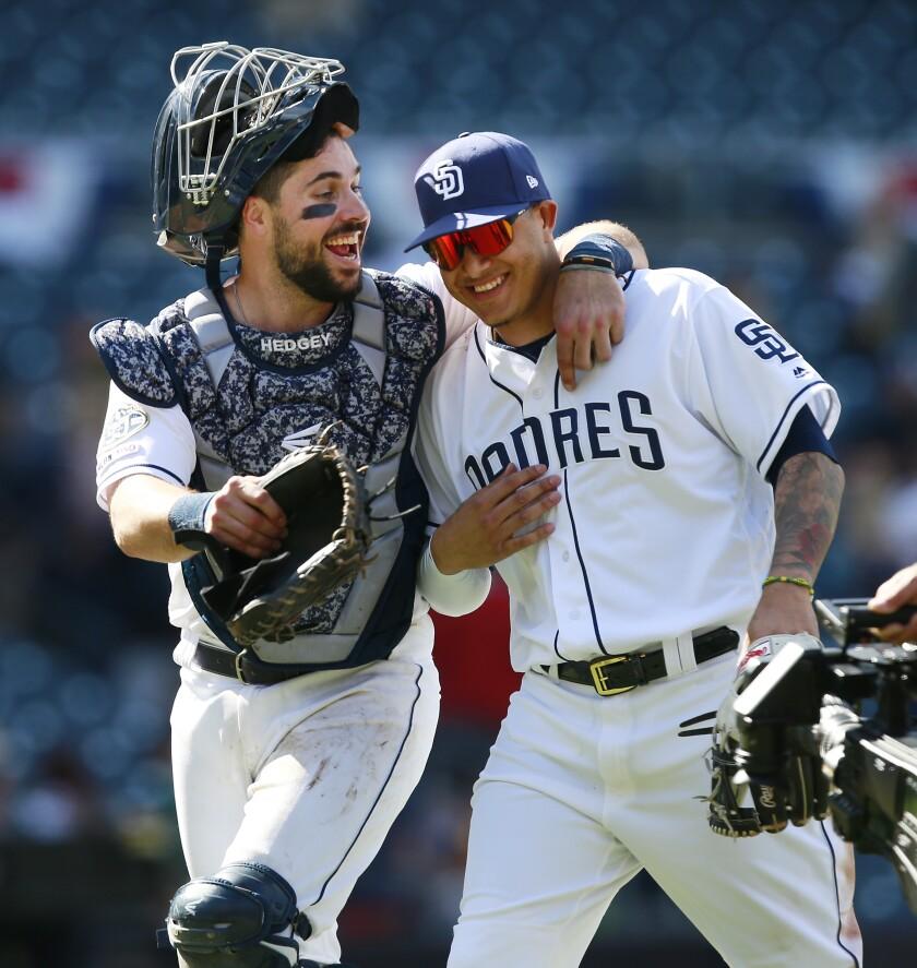 Padres catcher Austin Hedges and third baseman Manny Machado celebrate a victory over the Diamondbacks on Wednesday.