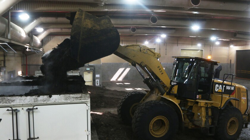 A front-loader dumps pre-treated sewage sludge into a mixer at Tulare Lake Compost in May.