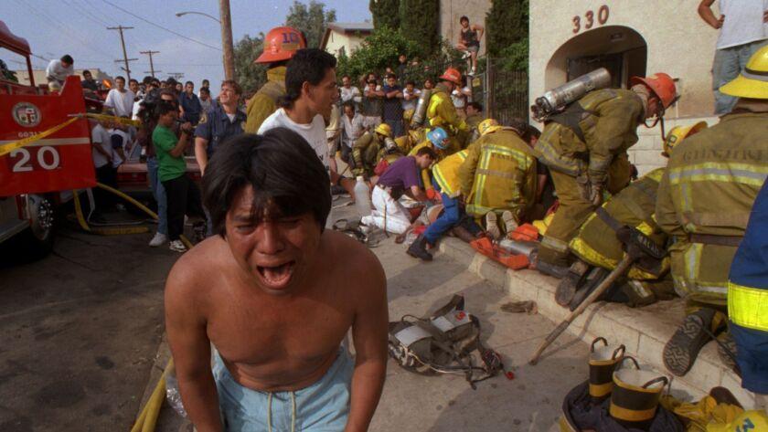 Un hombre llora luego de haber pasado a un lado del cuerpo de un niño, víctima del incendio en los apartamentos de Wastlake en 1993.