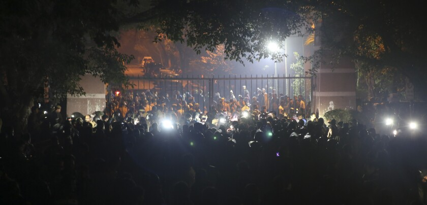 In this late Sunday, Jan.5, 2020 photo, police arrive outside the Jawaharlal Nehru University after masked assailants beat students and teachers with sticks in New Delhi, India. More than 20 people were injured in the attack opposition lawmakers are trying to link to the government. (AP Photo)
