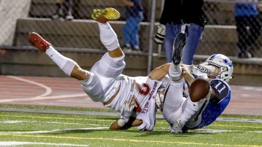 Rancho Bernardo defensive back Jonny Tanner strips the ball from Mission Hills wide receiver Skai Do
