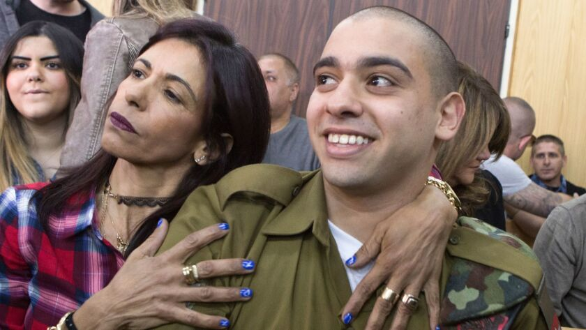 Israeli soldier Elor Azaria is embraced by his mother at the start of his sentencing hearing in Tel Aviv.