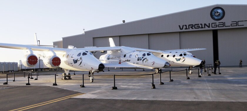 FILE - In this Sept. 25, 2013, file photo, the first SpaceShipTwo is seen suspended at center beneath its twin-fuselage mother ship at the Virgin Galactic hangar at Mojave Air and Space Port in Mojave, Calif. Virgin Galactic will roll out a new copy of its space tourism rocket Friday, Feb. 19, 2016
