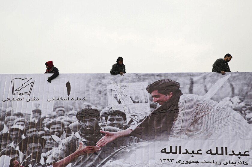 Afghans erect an election poster of presidential election candidate Abdullah Abdullah in Kabul on Sunday as campaigning officially opened.