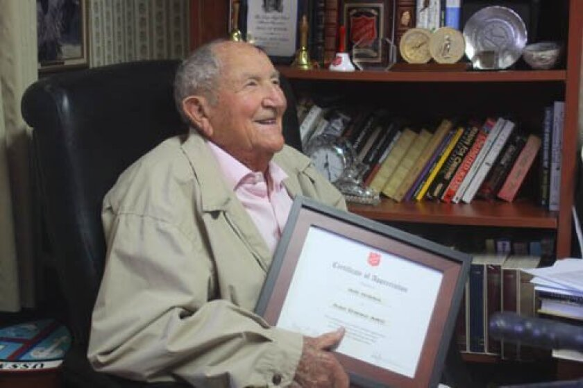 Bill Gibbs holds a Salvation Army certificate of appreciation in front of honors from local organizations like the Kiwanis Club of San Diego. Ashley Mackin photos