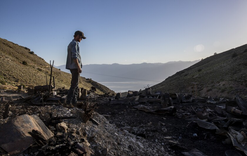 Brent Underwood stands amid the mountainside ashes of the American Hotel at Cerro Gordo, far above the desert below.