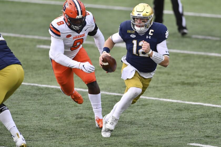 Notre Dame quarterback Ian Book (12) runs as Syracuse defensive lineman Jonathan Kingsley (9) pursues in the first half of an NCAA college football game Saturday, Dec. 5, 2020, in South Bend, Ind. (Matt Cashore/Pool Photo via AP)