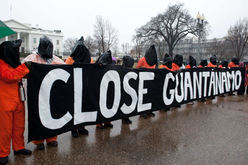 Protestors wear orange detainee jumpsuits and black hoods as they hold a banner calling for the closing of the US detention center at Guantanamo naval base in Cuba in front of the White House in Washington on January 11, 2014.
