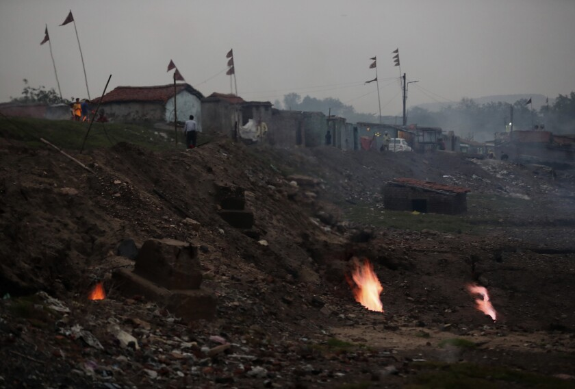In this Oct. 23, 2019, photo, flames rise out of the fissures on the ground above coal mines in the village of Liloripathra in Jharia, a remote corner of eastern Jharkhand state, India. The fires started in coal pits in eastern India in 1916. More than a century later, they are still spewing flames and clouds of poisonous fumes into the air, forcing residents to brave sizzling temperatures, deadly sinkholes and toxic gases. (AP Photo/Aijaz Rahi)