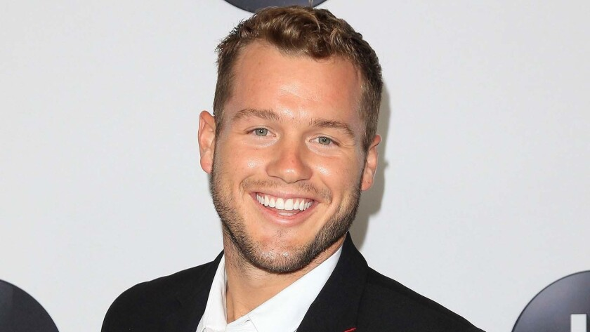 Colton Underwood smiling in a suit