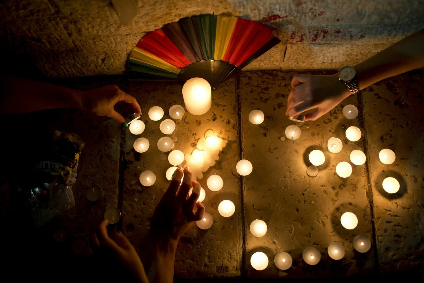 Members LGBT community light candles in solidarity with Florida's shooting attack victims, in Tel Aviv, Israel, Sunday, June 12, 2016.  The shooting attack in Orlando, Florida, USA, Sunday, left more than 50 people dead amid a multitude of events celebrating LGBT Pride Month. (AP Photo/Oded Balilty