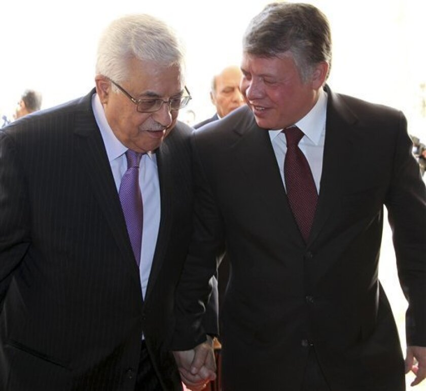 "In this photo provided by Jordanian News Agency PETRA, Palestinian President Mahmoud Abbas, left, holds hands with King Abdullah II of Jordan as they meet in Amman, Jordan, Tuesday, Jan. 10, 2012. President Abbas says talks between chief Palestinian and Israeli negotiators have provided an 'important opportunity' for reviving direct negotiations. ""We must take this chance,"" Abbas told reporters after talks with Jordan's King Abdullah II in Amman on Tuesday. (AP Photo/PETRA)"