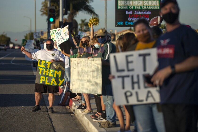 """Mike Pino, left, and others participate in a """"Let Them Play"""" rally at Edison High School on Friday."""