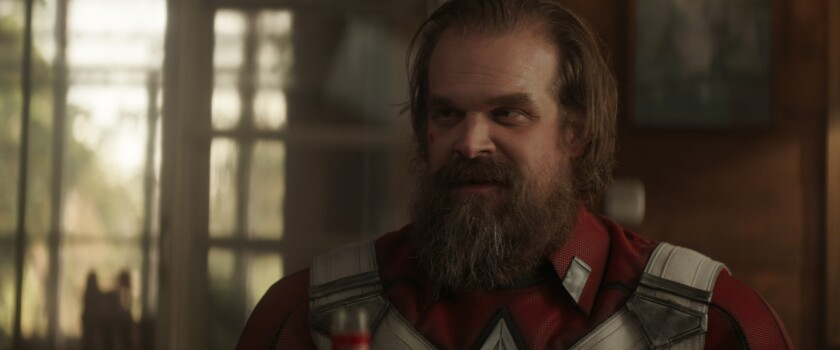 A man with a beard in a red and white costume
