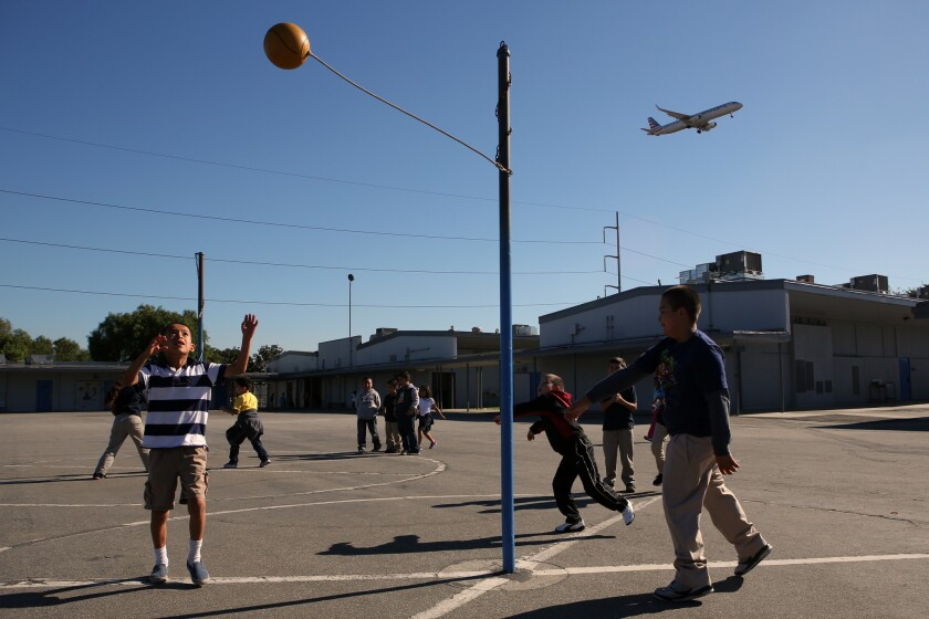 A plane flies over a residential area near Los Angeles International Airport.