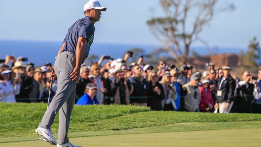 Tiger Woods reacts to missing a long eagle putt on his final hole Friday during the Farmers Insurance Open at Torrey Pines. He tapped in for birdie to make the cut.