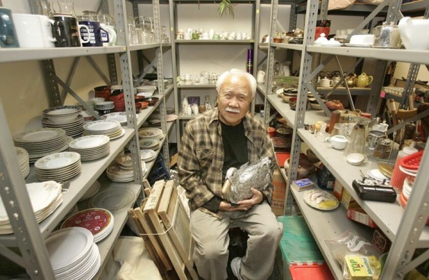 """Prop manager Ken Takemoto, holding a remote-control duck he created for a staging of """"Pippin,"""" is surrounded by odds and ends from East West Players productions. He has worked with the group since 1989."""
