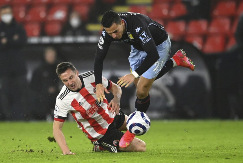 Aston Villa's Anwar El Ghazi, right, is fouled by Sheffield United's Phil Jagielka during the English Premier League soccer match between Sheffield United and Aston Villa at Bramall Lane stadium in Sheffield, England, Wednesday, March 3, 2021. (Clive Mason/Pool Photo via AP)