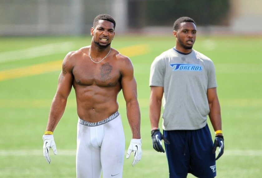SDSU's Eric Pinkins, left and USD's Fred Obi worked out in front of NFL coaches and scouts at SDSU's practice field.