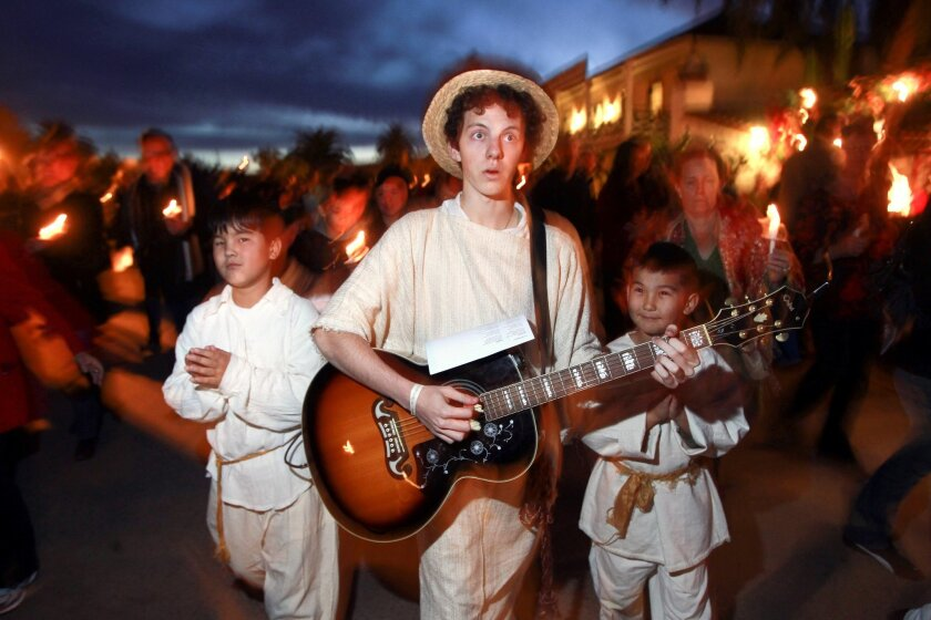 Austyn Myers, 17, sings and plays guitar while he, Eveylt Delger, 10, left, and Eveylt's younger brother Joshua Delger, 8, lead the procession as angels.