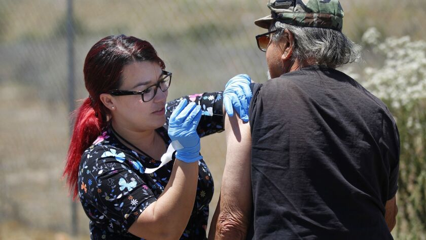"""Public Health Nurse Aysha Gari gives a Hepatitis A shot to Alfredo Francia, who lives in a motor home in Lakeside, on May 17, 2018. Gari was a member of San Diego County's mobile """"foot team"""" force that was instrumental in getting the region's hepatitis outbreak under control."""