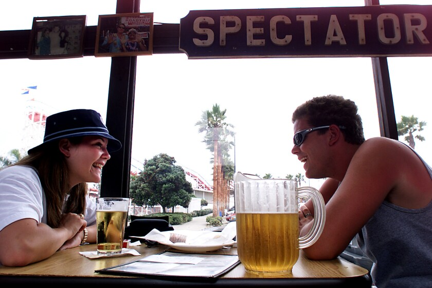 Arizona State University students Sarah Fluhr, left, and Cody Hoge share a laugh and brew at a local Mission Beach pub in San Diego, the top destination for Southern Californians this Labor Day weekend.
