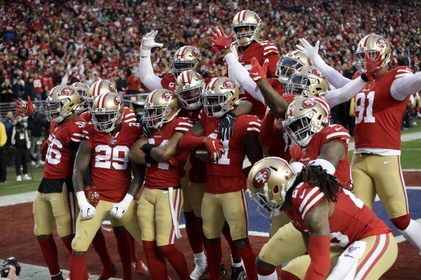 The 49ers defense celebrates after defensive back Emmanuel Moseley's interception of Packers quarterback Aaron Rodgers during the first half of the NFC championship game.
