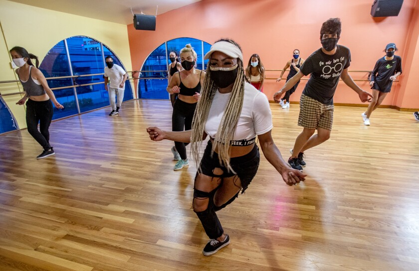 A dancer in a white shirt and jeans teaches a hip hop dance class to a room of 8 other dancers.