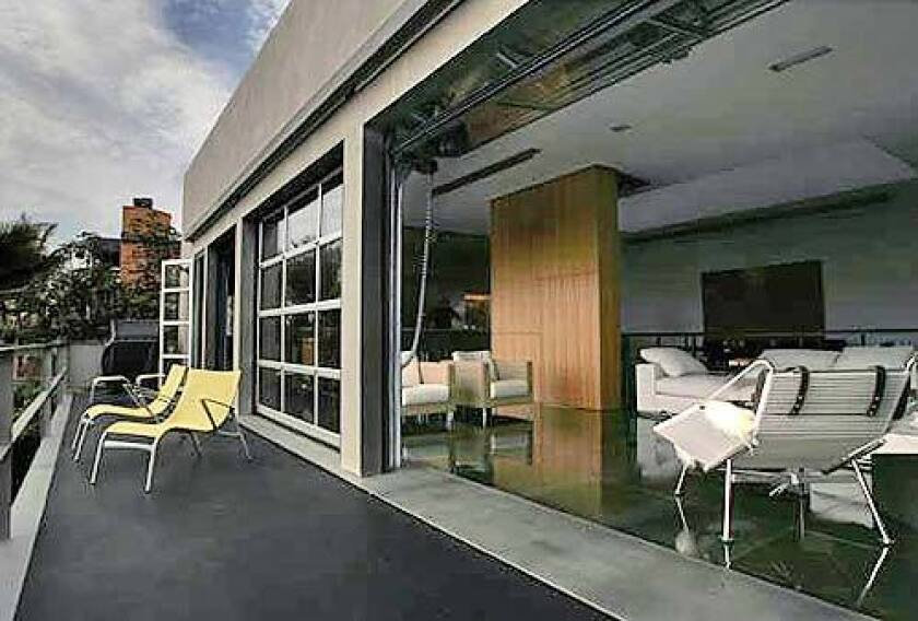 Aluminum-and-glass doors inspired by British firehouses and made in the United Kingdom fold upward electronically to bring the outdoors into the living room.