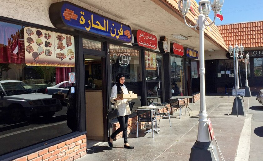 """A woman wearing a traditional Muslim head covering exits a Lebanese eatery in Orange County's """"Little Arabia"""" neighborhood just miles from Disneyland.Orange County's """"Little Arabia"""" neighborhood in Anaheim, Calif., Wednesday, March 23, 2016. After Sen. Ted Cruz called for increased surveillance of Muslims in the U.S., this Muslim community and others like it defied the Republican presidential candidate and defended their commitment to the United States. (AP Photo/Gillian Flaccus)"""
