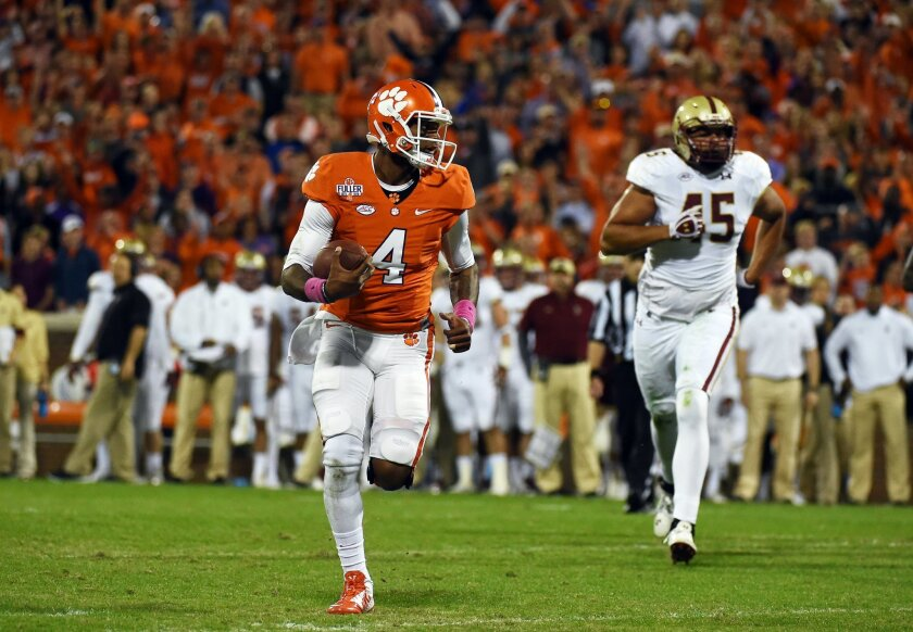 FILE - In this Oct. 17, 2015, file photo, Clemson quarterback Deshaun Watson (4) runs for a touchdown as Boston College defensive lineman Mehdi Abdesmad (45) trails during the first half of an NCAA college football game in Clemson, S.C. In the year of the running back, Watson is making a late push to keep the Heisman Trophy in a quarterback's hands. (AP Photo/Rainier Ehrhardt, File)