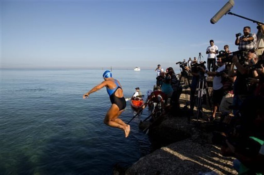 U.S. swimmer Diana Nyad, 64, jumps into the water to begin her swim to Florida from the waters off Havana, Cuba, Saturday, Aug. 31, 2013. Endurance athlete Nyad launched another bid Saturday to set an open-water record by swimming from Havana to the Florida Keys without a protective shark cage. (AP