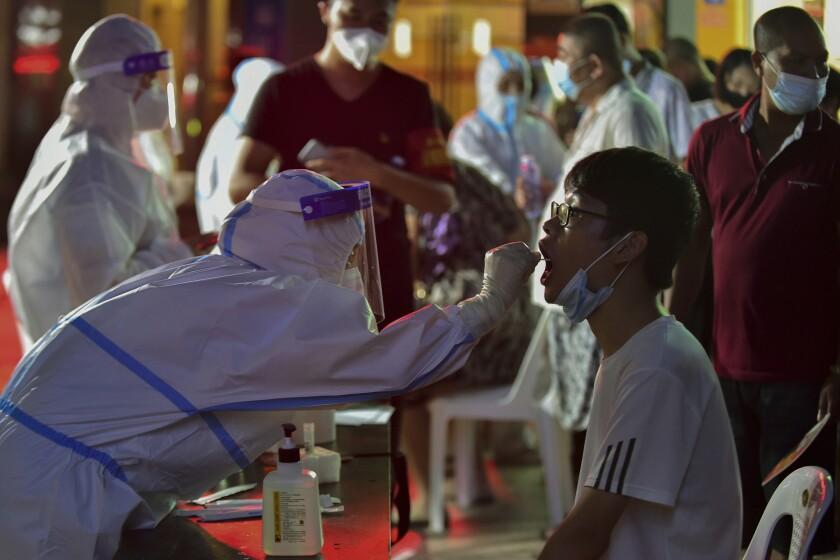 En esta imagen, distribuida por la agencia de noticias Xinhua, un trabajador sanitario toma una muestra