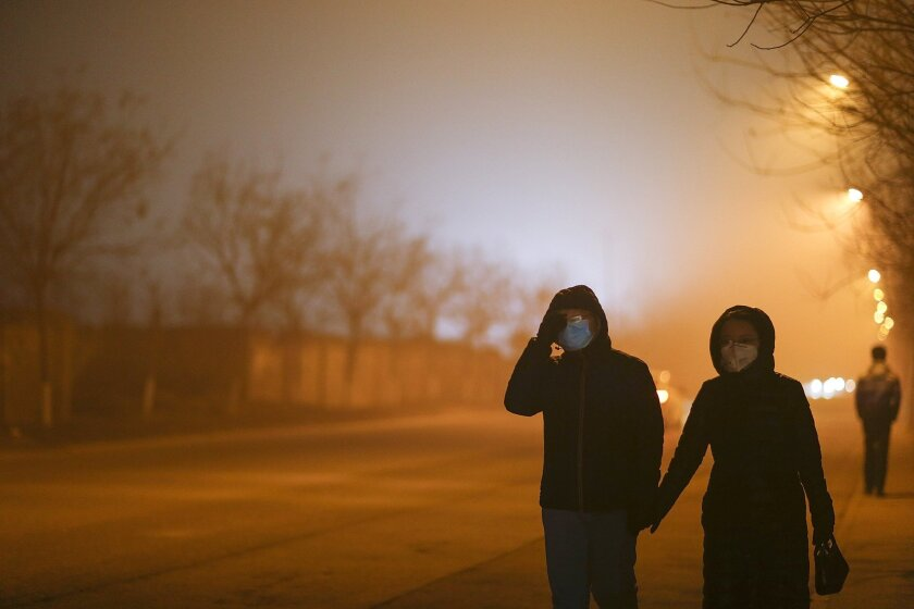 People walk through Beijing wearing masks on Dec. 22, a heavy pollution evening.