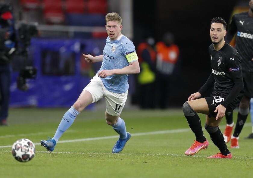 Kevin De Bruyne del Manchester City pasa el balón frente a Ramy Bensebaini
