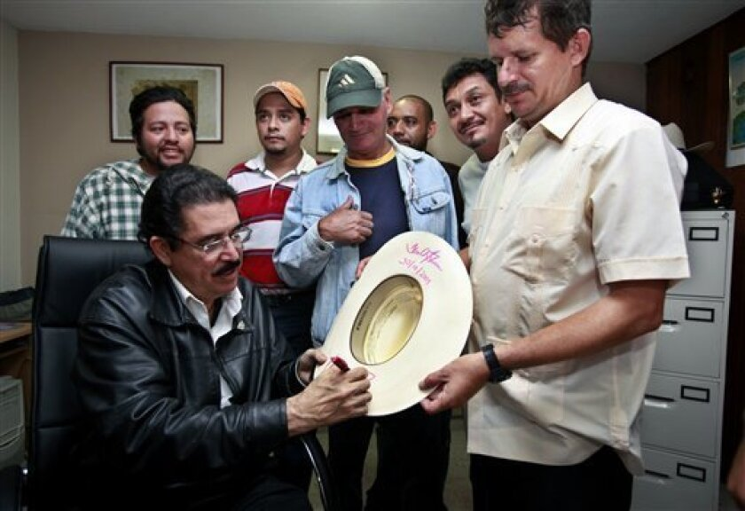 Honduras' ousted President Manuel Zelaya, bottom left, signs an autograph on a hat of a supporter at the Brazilian embassy in Tegucigalpa, Friday, Oct. 30, 2009. A top regional diplomatic official said negotiators for Honduras' interim and ousted leaders have signed an agreement that allows for the possible return of Zelaya. (AP Photo/Esteban Felix)