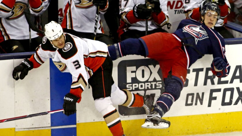 Ducks defenseman Kevin Bieksa (3) and Blue Jackets left wing Sonny Milano (22) crash into the boards after a collision during the first period Friday night in Columbus.