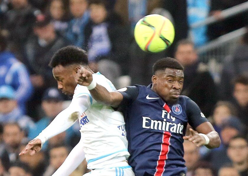Paris Saint Germain's Serge Aurier, right,  challenges for the ball with Marseille's Georges-Kevin NKoudou, during the League One soccer match between Marseille and Paris Saint-Germain, at the Velodrome Stadium, in Marseille, southern France, Sunday, Feb. 7, 2016. (AP Photo/Claude Paris)
