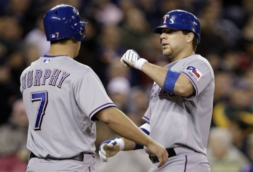 Texas Rangers' Chris Davis, right, is greeted by David Murphy at home on Davis' two-run home run against the Seattle Mariners in the sixth inning during a baseball game Monday, May 4, 2009, in Seattle. (AP Photo/Elaine Thompson)