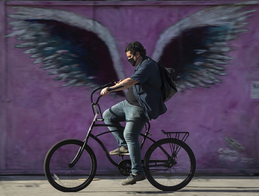 A cyclist pedals past a mural on Melrose Avenue.