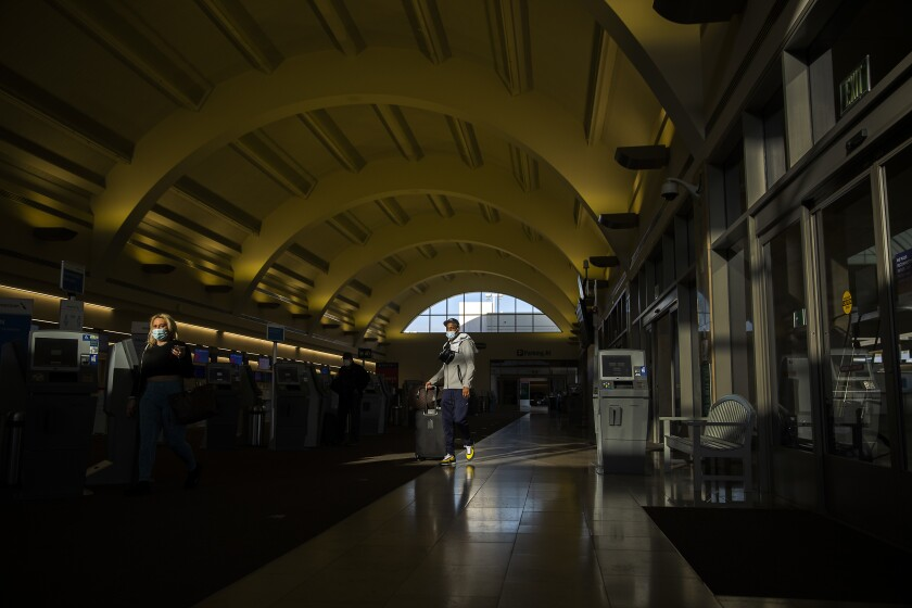 Travelers wear masks as they make their way through John Wayne Airport in Santa Ana on Monday.