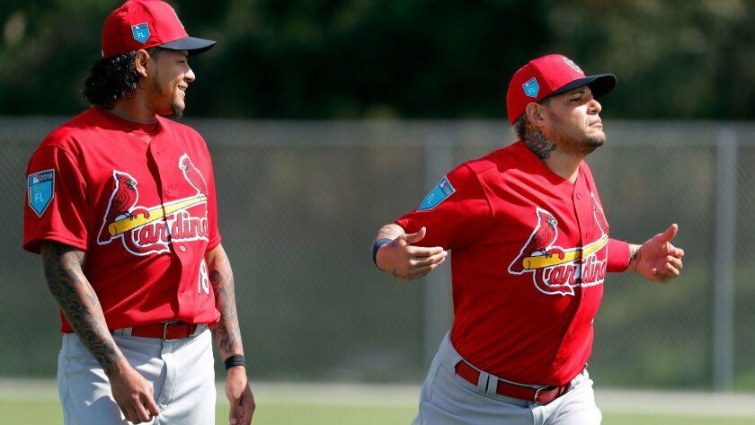 St. Louis Cardinals' Yadier Molina, right, jokes around while stretching as teammate Carlos Martinez
