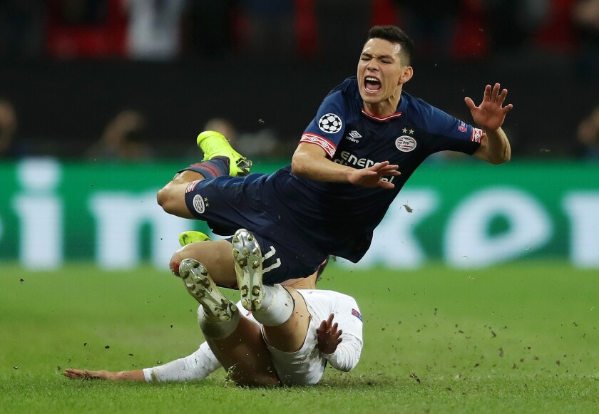 Hirving Lozano of PSV Eindhoven is tackled by Heung-Min Son of Tottenham Hotspur during the Group B match of the UEFA Champions League between Tottenham Hotspur and PSV at Wembley Stadium on November 6, 2018 in London, United Kingdom.