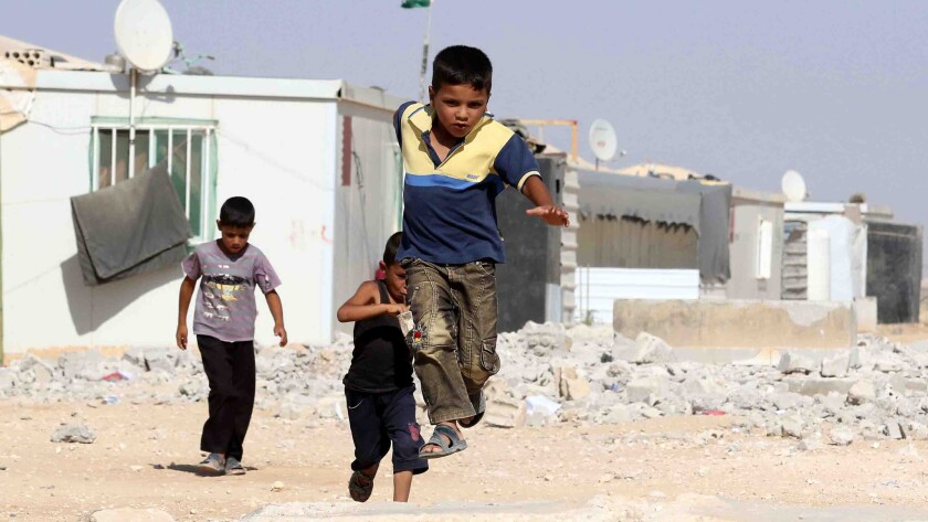 Syrian refugee children play at the Zaatari refugee camp, located close to the northern Jordanian city of Mafraq near the border with Syria.